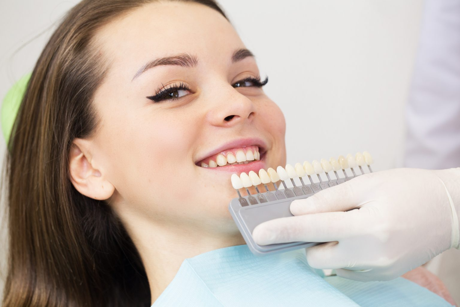 Close Up Portrait Of Young Women In Dentist Chair, Check And Select The Color Of The Teeth. Dentist Makes The Process Of Treatment In Dental Clinic Office