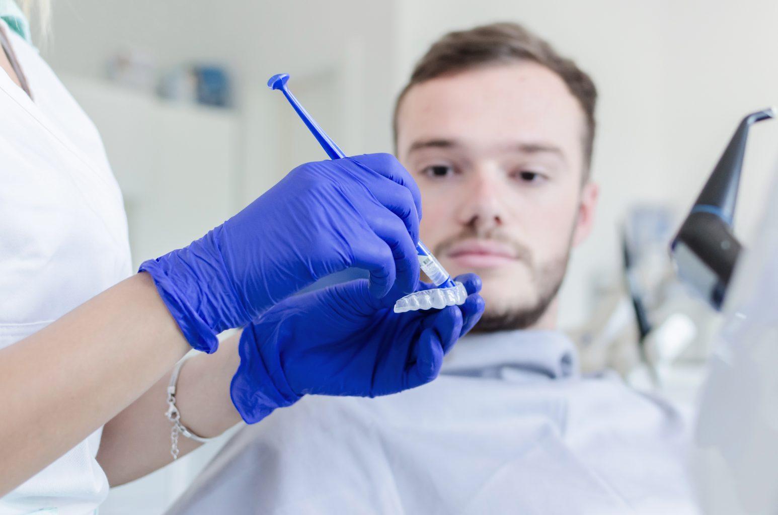Man Whitening Teeth In Dental Office