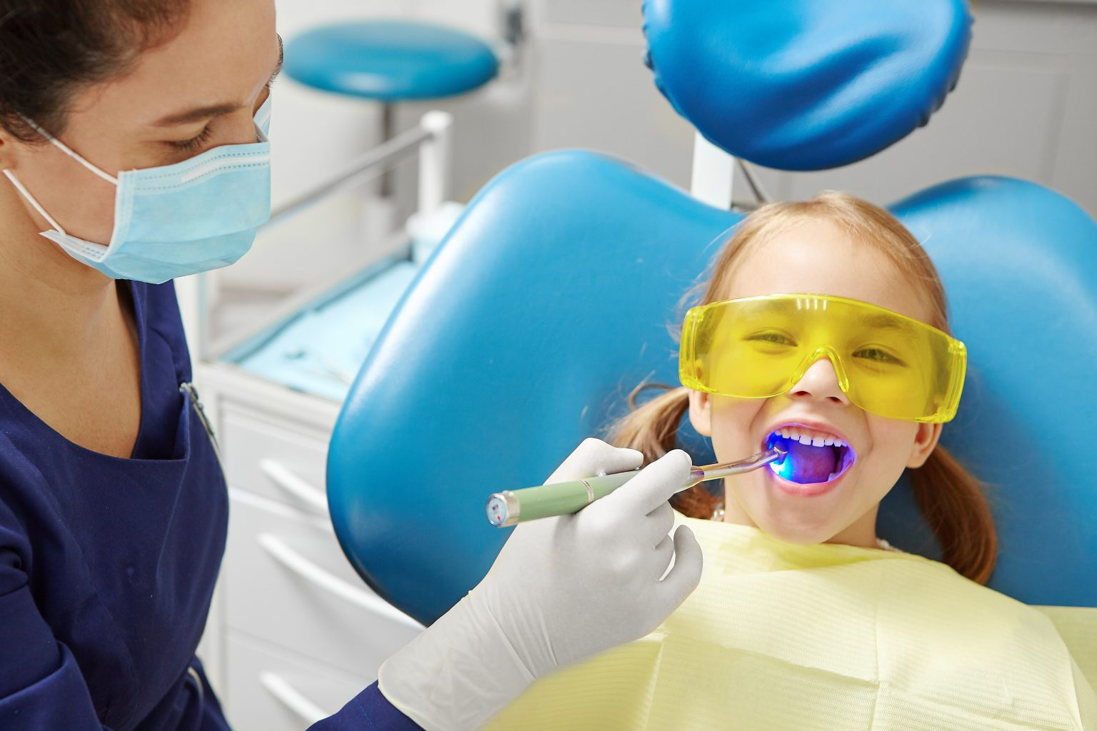 Process Of Drying The Dental Seal After Treatment Of The Patient's Tooth In Pediatric Dentistry. Little Girl In Dentist Office.